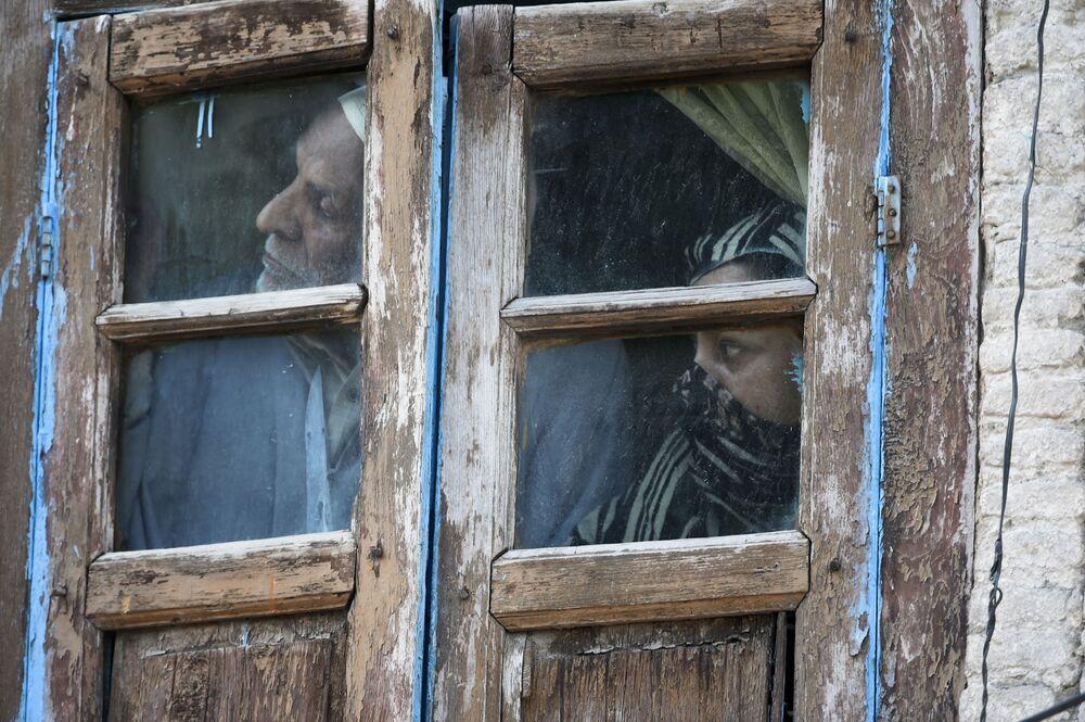 سكان يراقبون من نافذتهم في منطقة بالقرب من موقع الاشتباكات بالأسلحة النارية بين مسلحين مشتبه بهم والقوات الحكومية في سريناغار، 19 مايو 2020.