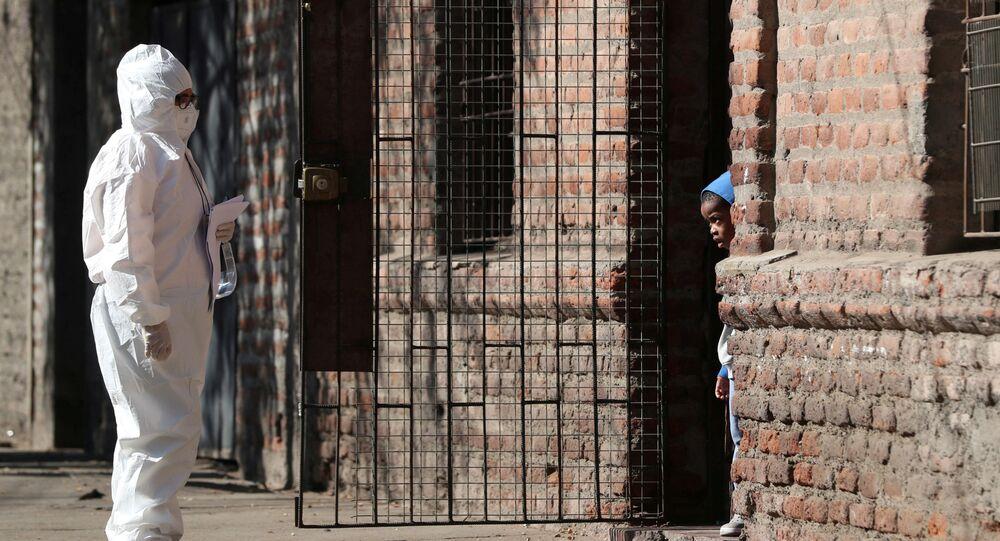 امرأة ترتدي بدلة واقية تتحدث إلى طفل في حي للمهاجرين، أثناء بدء الحجر الصحي العام، بسبب الأعداد المتزايدة من حالات الإصابة بفيروس كورونا في مدينة سانتياغو، تشيلي 16 مايو 2020.
