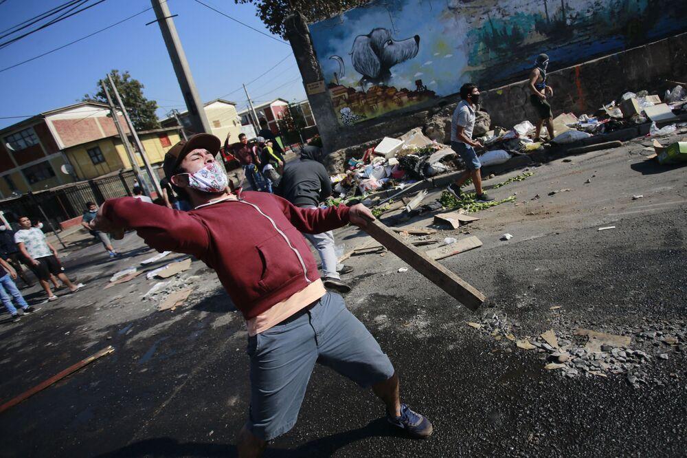 اشتباك بين متظاهرين مع شرطة مكافحة الشغب خلال احتجاجات ضد حكومة الرئيس التشيلي سيباستيان بينيرا نقص الغذاء والعمل نتيجة للأزمة الناجمة عن الفيروس والحجر الصحي، وسط جائحة كورونا في سانتياغو ، في 18 مايو 2020