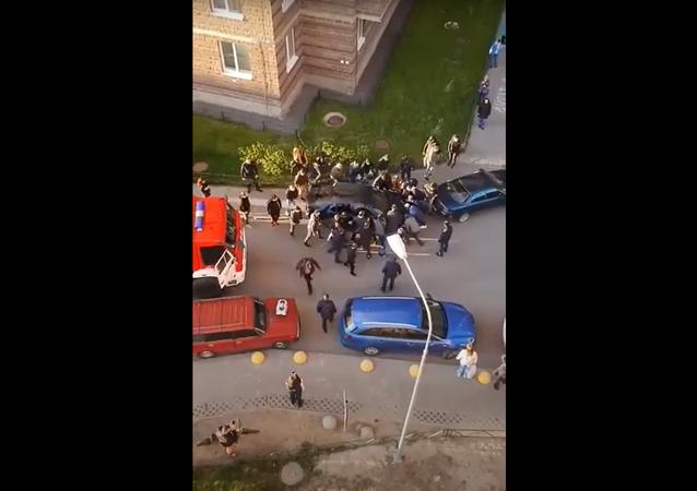حشد من الرجال يبعدون سيارة بأيديهم العارية لتمرير سيارة الإطفاء