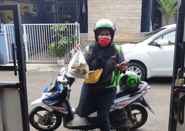 امرأة في إندونيسيا تركب دراجة نارية لتوصيل الطعام