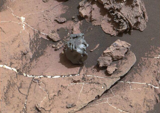 صورة لصخرة ملساء داكنة اللون، التقطتها كاميرا تصوير ماست كاميرا (Mast Camera) المثبتة على المركبة المتجولة على المريخ كيوريوسيتي روفر، والتي أثبتت تحليلها الحاسوبي أن الصخرة جزء من نيزك مكوانته الحديد والنيكل. 30أكتوبر/ تشرين أول 2016