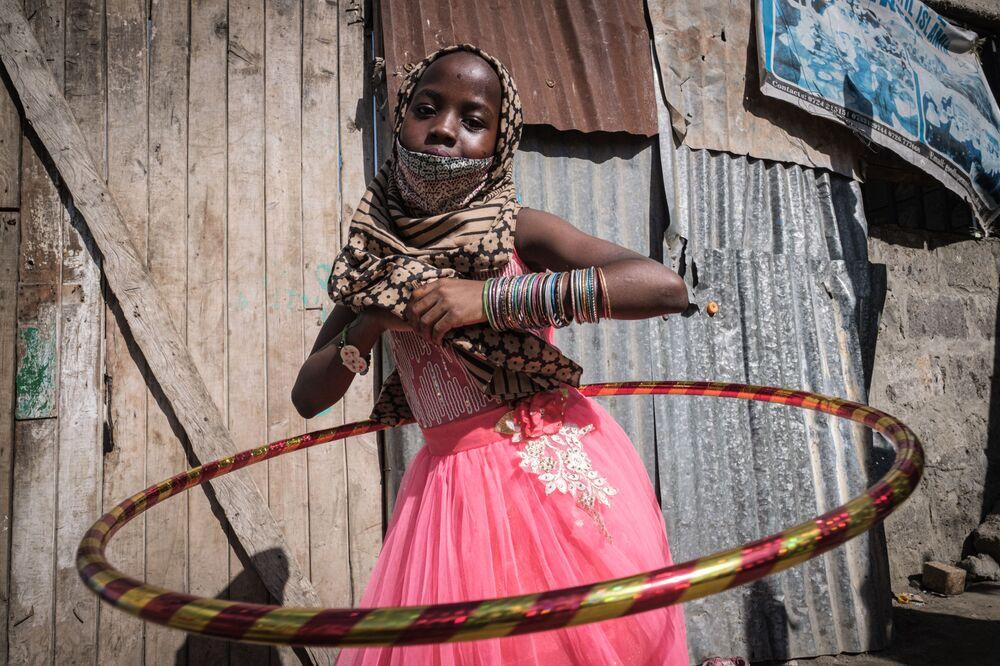 فتاة يتيمة تلعب الهولاهوب أثناء توزيع الطعام والألعاب على الأيتام في 11 دار للأيتام بمناسبة عيد الفطر في كينيا، 25 مايو/ أيار 2020