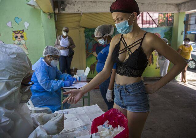 امرأة أثناء القيام بالاختبار السريع لمرض كوفيد-19، الذي يجريه موظفو وزارة الصحة العامة في حي دي فيبيرو في سانتو دومينغو، جمهورية الدومنيكان  في 25 مايو/ أيار 2020.