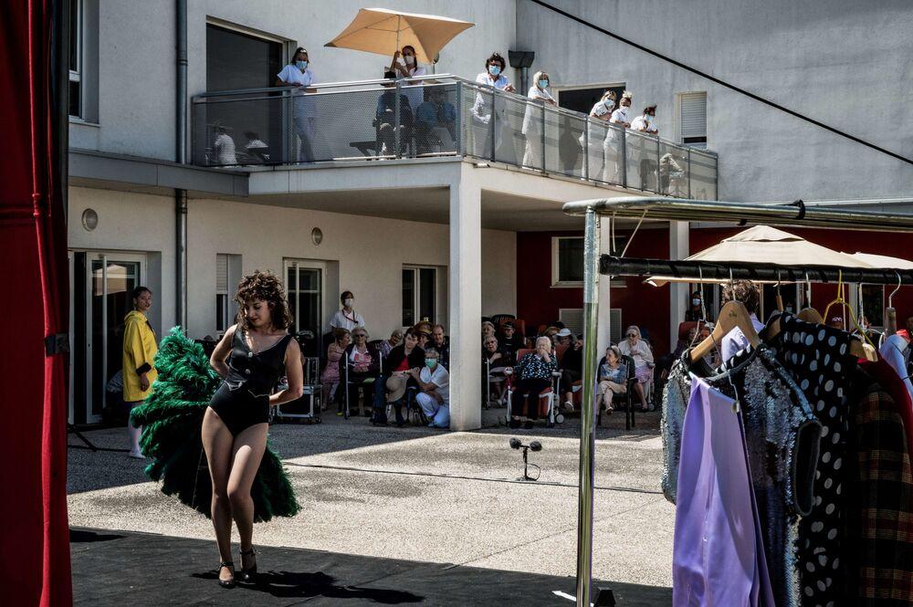 ممثلو مؤسسة مسرح L'Espace des Arts company يؤدون عرضا للمقيمين في دار  للمسنين بويس دي مينوس، فرنسا 26 مايو/ أيار 202 في بلدة شالون-سور-ساون وسط أزمة بالجائحة كوفيد-19.