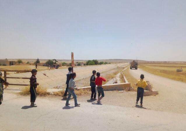 أطفال سوريين يطردون رتلا أمريكيا بريف الحسكة