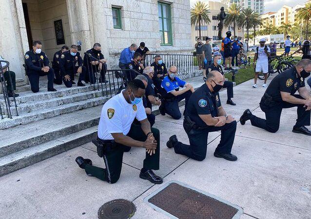 احتجاجات جورج فلويد - عناصر الشرطة الأمريكية يقفون على ركبة واحدة في إطار التضامن مع المتظاهرين في ميامي، الولايات المتحدة