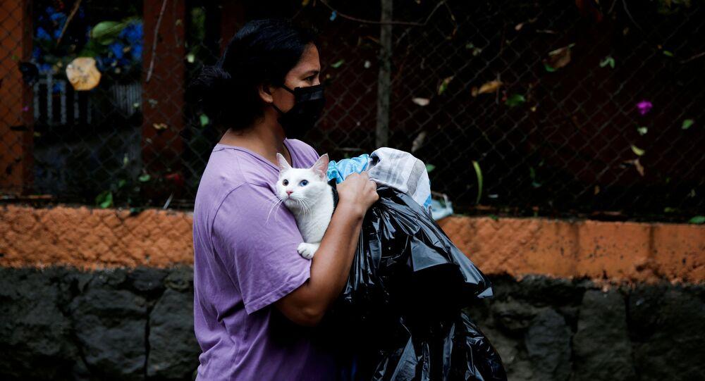 امرأة ترتدي كمامة حاملة قطها أثناء فياضانات سببها إعصار أماندا في مدينة إلوبانغو، سلفادور 31 مايو 2020