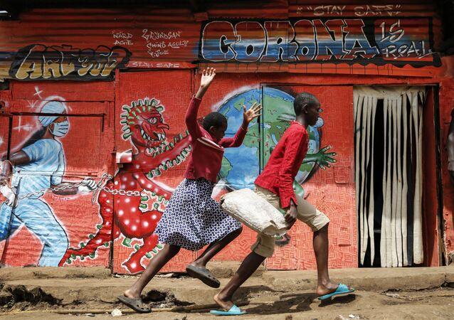 أطفال يركضون على خلفية غرافيني كورونا في نيروبي، كينيا 3 يونيو 2020