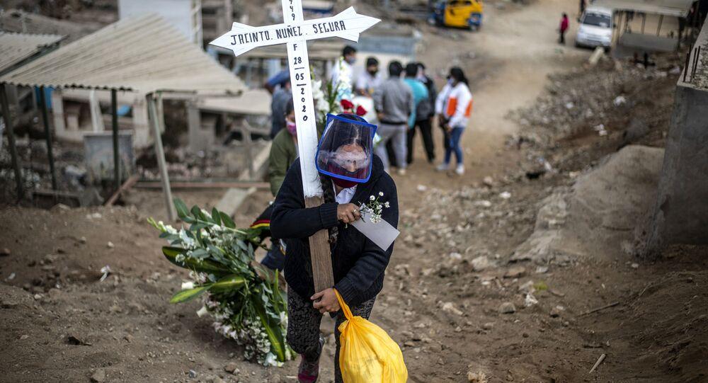 أحد أقرباء ضحايا كوفيد-19 يحمل صلبيا في مقبرة في ضواحي مدينة ليما، بيرو 30 مايو 2020