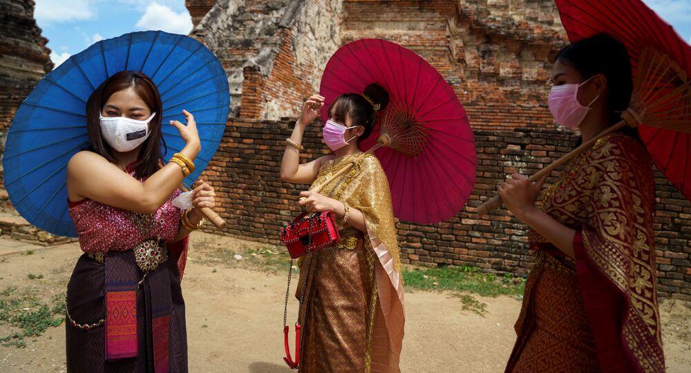 نساء يرتدين كمامات وأزياء تقليدية أثناء زيارة  إلى معبد وات شايواتثانارام بعد أن خففت الحكومة التايلاندية من إجراءات الحجر المنزلي المفروض لمنع الإصابة بمرض كوفيد-19 في مدينة أيوتثايا، تايلاند، 1 يونيو 2020