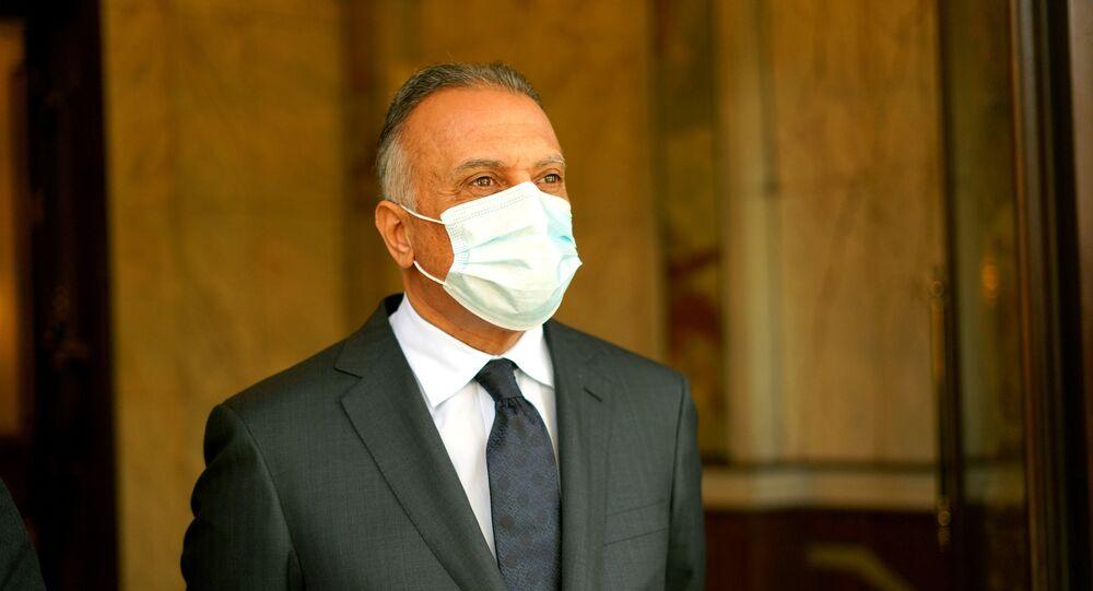 رئيس الوزراء العراقي مصطفى الكاظمي يقف في مكتبه في بغداد وهو يرتدي قناعا للوجه بعد تفشي فيروس كورونا