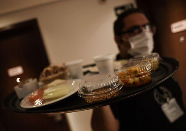 نادل مرتدي كمامة طبية يحضر الطعام في غرفة بفندق