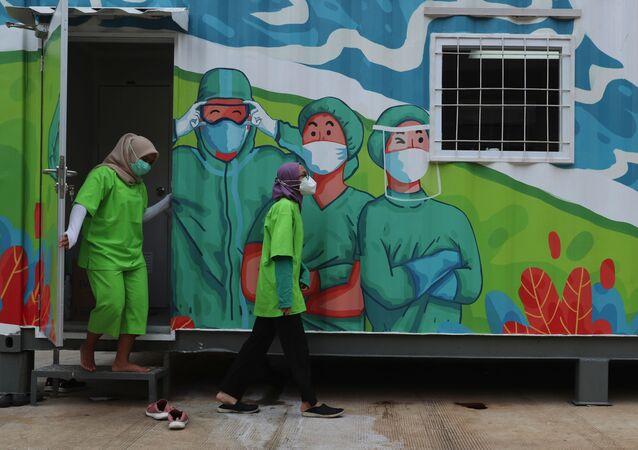 العاملون في القطاع الصحي يخرجون من مختبر متنقل قبل تحليل العينات التي تم جمعها خلال اختبارات عامة لفيروس كورونا في جاكرتا، إندونيسيا، 18 يونيو 2020