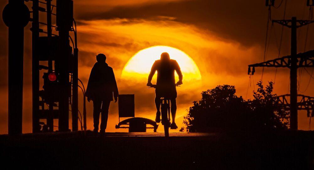 رجل يركب دراجة هوائية في حديقة على خلفية غروب الشمس، حيث دخلت موسكو المرحلة الثانية من رفع القيود المفروضة بسبب كورونا، 14 يونيو 2020
