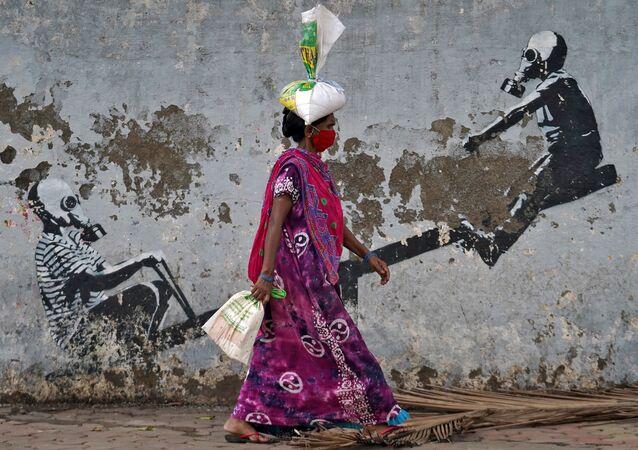 امرأة ترتدي كمامة تسير في أحد شوارع مدينة مومباي، بعد أن أعلنت السلطات المحلية بتخفيف الإغلاق العام بسبب تفشي المرض الفيروسي كوفيد-19، الهند، 12 يونيو 2020