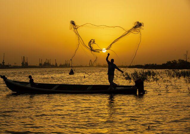 صياد السمك يلقي بشبكته عند الغروب في مياه نهر شط العرب في مدينة البصرة، العراق 12 يونيو 2020