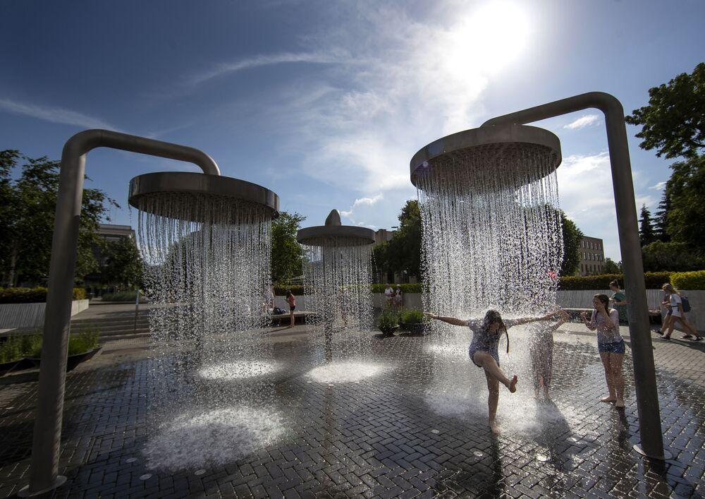 أطفال يلعبون بين نوافير المياه في مدينة فيلنوس، خلال موجة حر تضرب ليتوانيا 19 يونيو 2020
