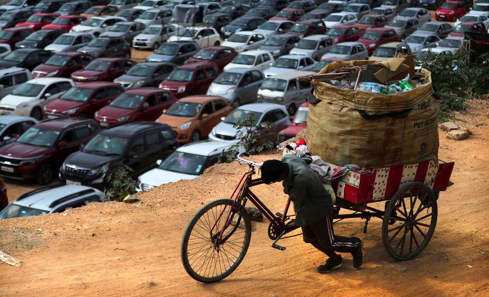 جامع القمامة والخردة يدفع بدراجته ذات الثلاث عجلات، بينما يجلس المسيحيون في سياراتهم الخاصة في إطار الحفاظ على التباعد الاجتماعي، خلال صلاة في كنيسة بيثال أ غ بنغالورو، الهند، الأحد 21 يونيو 2020.