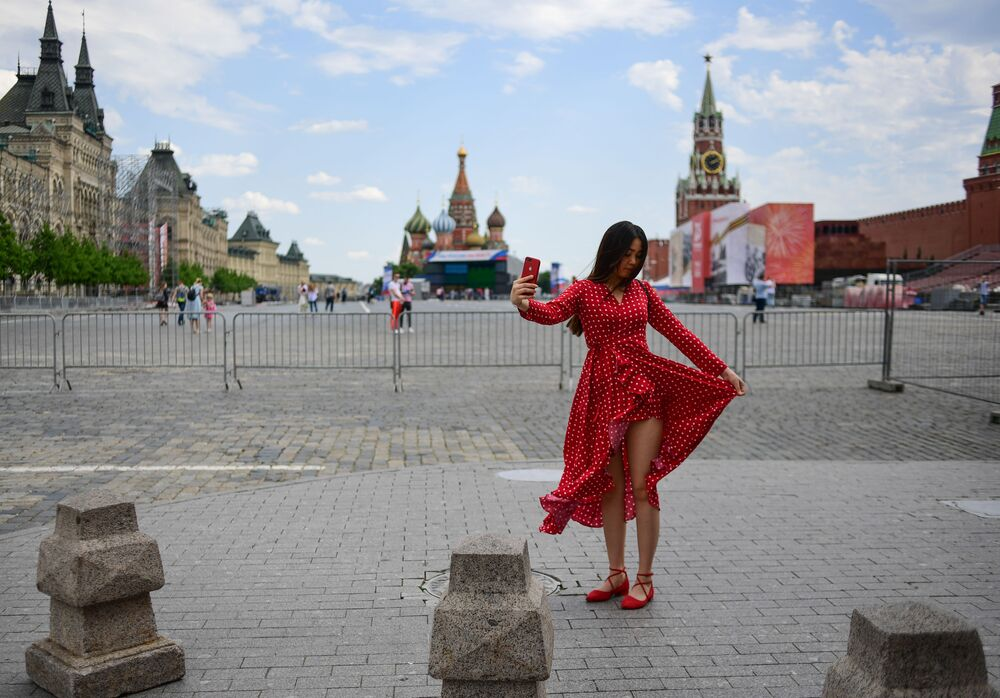 امرأة تلتقط صورة سيلفي على خلفية الساحة الحمراء في يوم مشمس في موسكو، روسيا 10 يونيو 2020