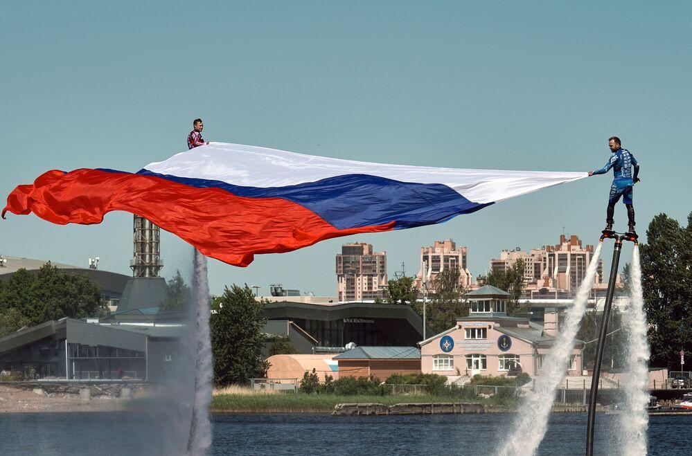 الرياضيون من المنتخب الوطني الروسي في Hydroflight (الدفع النفاث المائي) يفتتحون مراسم الاحتفال بيوم روسيا برفع العلم في سان بطرسبورغ.