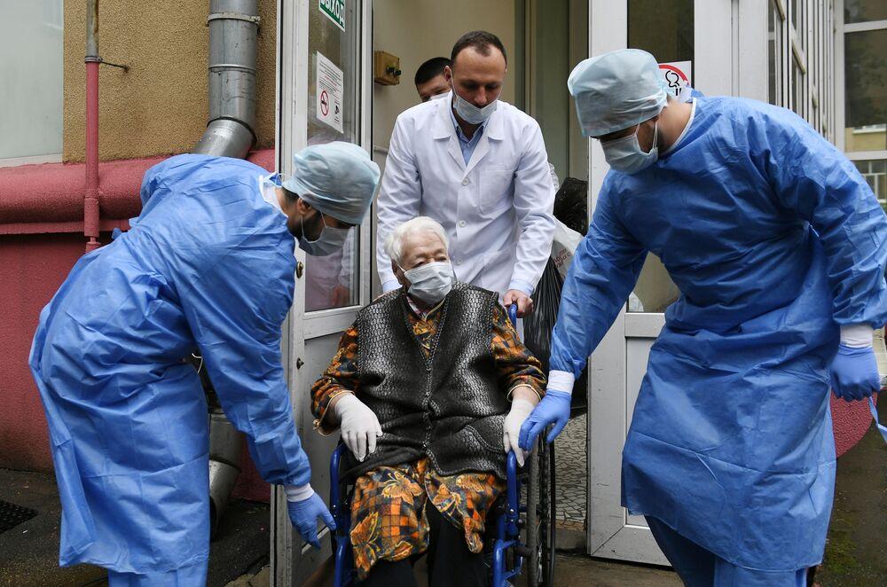 مريضة، زينايدا أفاناسيفنا نوفيكوفا، تبلغ من العمر 101 عامًا، أثناء خروجها من المشفى، بعد تلقي علاج عدوى الفيروس التاجي كوفيد- 19 وانتصارها على المرض، موسكو 2 يونيو 2020