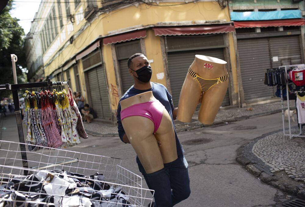 بائع يرتدي كمامة للحد من انتشار فيروس كورونا، يحمل العارضات التي تعرض بدلات السباحة، في سوق أحد شوارع  ريو دي جانيرو، البرازيل 29 يونيو 2020. سمحت سلطات ريو في نهاية هذا الأسبوع للتجارة وصالونات التجميل بفتح أبوابها للزبائن حيث بدأت السلطات بتخفيف الاجراءات الاحترازية في المدينة بعد إغلاقها وسط تفشي الوباء.