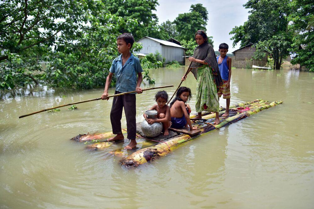 قرويون يجرون طوفًا مؤقتًا عبر حقل غمرته المياه للوصول إلى مكان أكثر أمانًا في قرية مايونغ المتضررة من الفيضانات في منطقة موريغاون، في ولاية آسام الشمالية الشرقية، الهند  29 يونيو 2020.