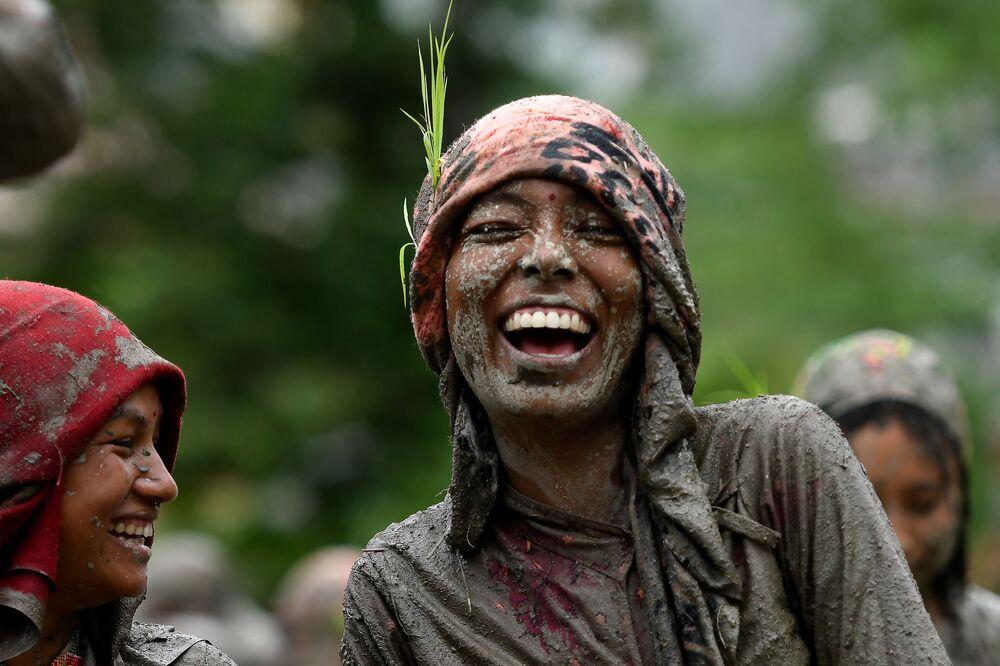 امرأة تبتسم في حقل أرز خلال يوم الأرز الوطني، الذي يمثل بداية موسم زراعة الأرز السنوي، في قرية توكا على مشارف كاتماندو في 29 يونيو 2020.