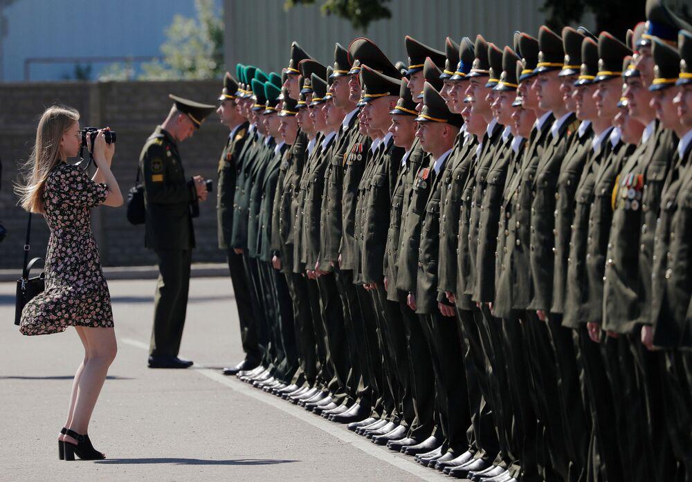 امرأة تلتقط صورًا للخريجين أثناء مراسم توزيع الدبلوم في الأكاديمية العسكرية في بيلاروسيا، وسط تفشي مرض فيروس التاجي كوفيد-19 في مينسك، بيلاروسيا، 27 يونيو 2020.