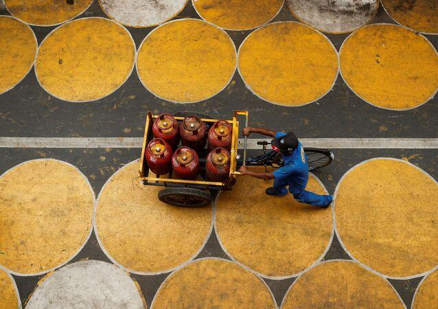 رجل يدفع عربة مملوءة بأسطوانات غاز البترول المسال في شارع فيه دوائر للمارة للحفاظ على التباعد الاجتماعي بعد تخفيف بعض القيود بعد إغلاق تام فرض لإبطاء انتشار مرض (COVID-19) في مومباي، الهند، 1 يوليو 2020.