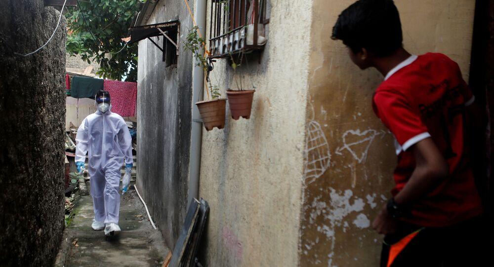موظف في القطاع الصحي يتفقد المواطنين لاجراء اختبار فيروس كورونا في مومباي، الهند، 1 يوليو 2020.