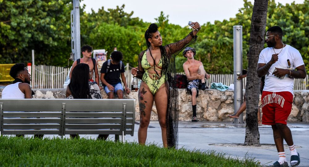 امرأة تلتقط صورة سيلفي لها مع أصدقائها في ميامي بيتش، بعد رفع قيود الحجر الصحي في فلوريدا في 26 يونيو 2020