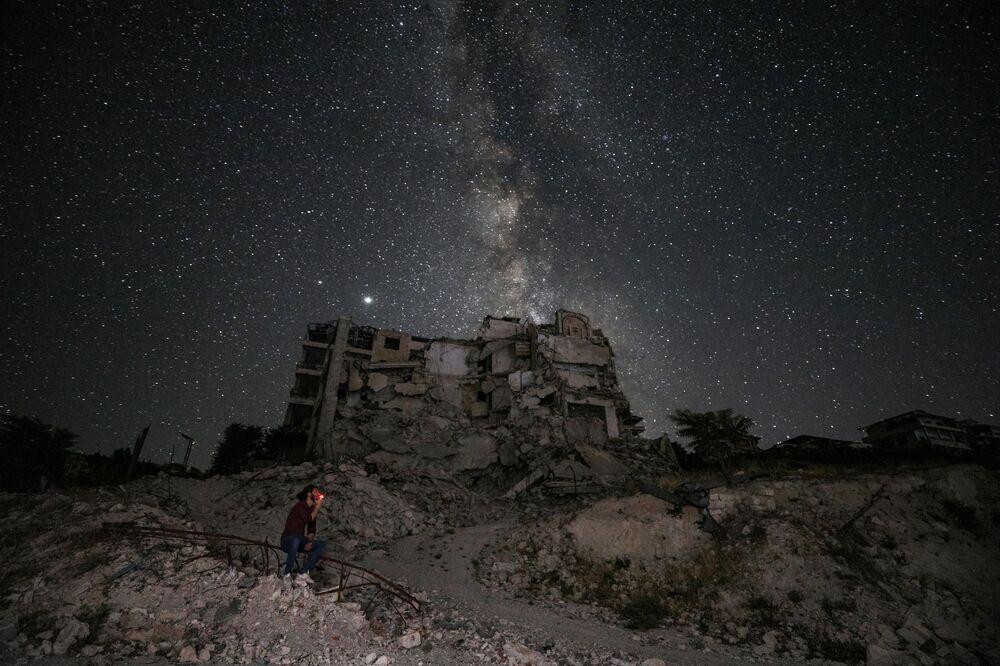 ركام مباني دمرت جراء قصف في بلدة أريحا،على خلفية السماء المرصعة بالنجوم ومجرة درب الدبانة في محافظة إدلب السورية، سوريا 27 يونيو 2020.