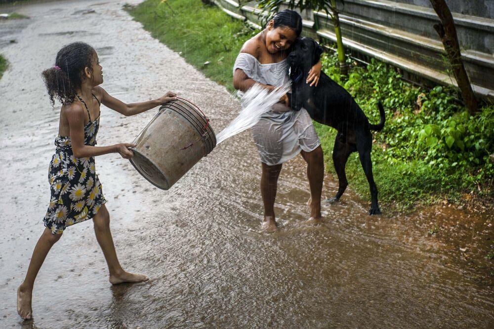 فتاة تلقي الماء على صديقتها وهي تلعب تحت المطر في هافانا، كوبا، 1 يوليو 2020.