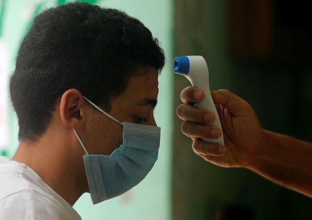 طبيب يفحص طالبا في الثانوية العامة قبل دخوله قاعة الامتحانات النهائية، وسط مخاوف من تفشي مرض كوفيد-19 في القاهرة، مصر، 21 يونيو 2020