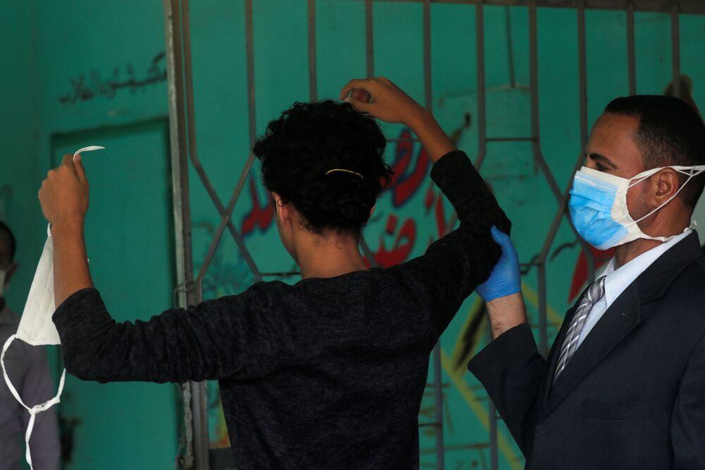 حارس مدرسة يفحص طالبا في الثانوية العامة قبل دخوله قاعة الامتحانات النهائية، وسط مخاوف من تفشي مرض كوفيد-19 في القاهرة، مصر، 21 يونيو 2020