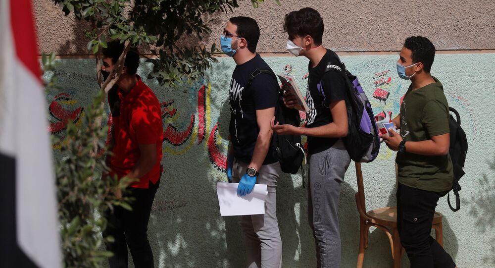 طلاب في الثانوية العامة يرتدون كمامات ينتظرون دورهم في الدخول إلى قاعة الامتحانات النهائية، وسط مخاوف من تفشي مرض كوفيد-19 في القاهرة، مصر، 21 يونيو 2020