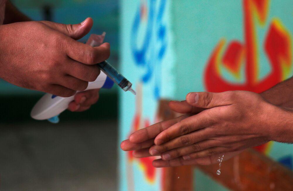 طالب في الثانوية العامة يعقم يديه قبل دخول قاعة الامتحانات النهائية، وسط مخاوف من تفشي مرض كوفيد-19 في القاهرة، مصر، 21 يونيو 2020