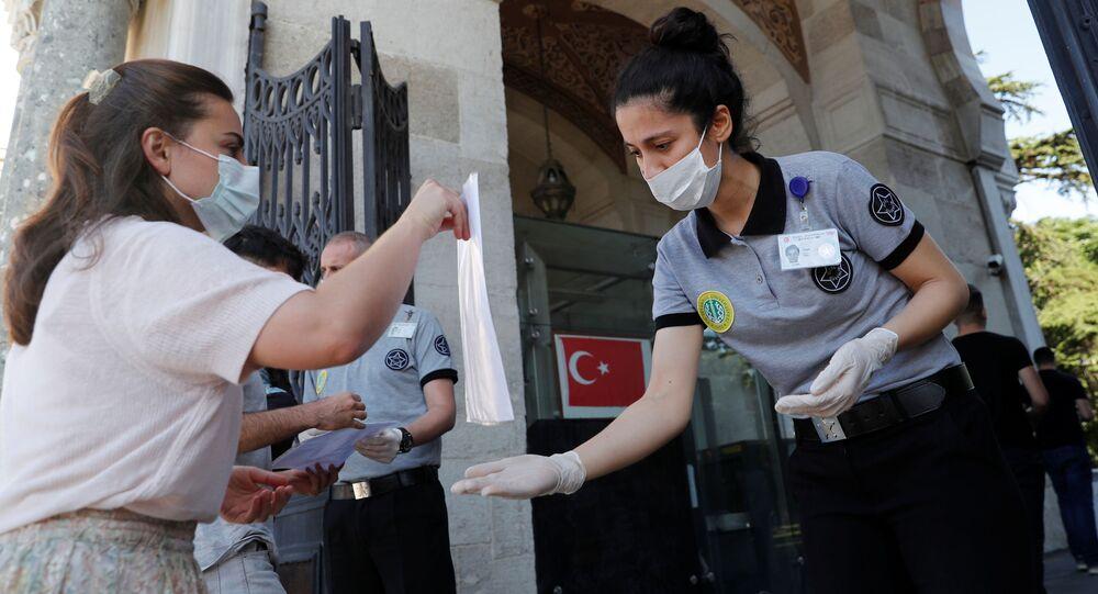 طالبة ترتدي كمامة تظهر يطاقتها الثبوتية لدى وصولها إلى الحرم الجامعي الرئيسي لجامعة إسطنبول لإجراء امتحانات القبول بالجامعة الوطنية، وسط انتشار مرض فيروس التاجي كوفيد-19) في اسطنبول، تركيا 27 يونيو 2020