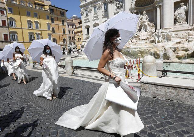 النساء اللواتي تم تأجل حفل زفافهن أو ألغي، نتيجة للقيود التي فرضتها البلاد بسبب تفشي فيروس كورونا، يحتجون أمام نافورة تريفي في روما، إيطاليا 7 يوليو  2020