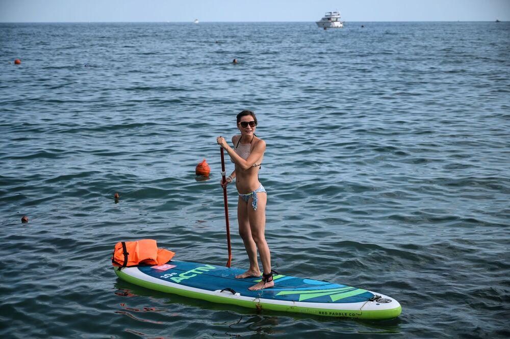 فتاة تقف على لوح لركوب الأمواج في المنتجع الصيفي تسيرك في سوتشي